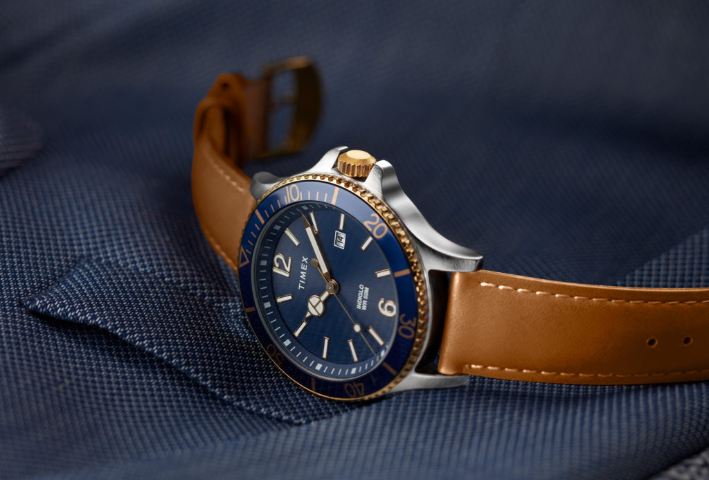 Silver and blue watch with brown leather straps and blue inner face with gold and white dials laying sideways on a blue blazer