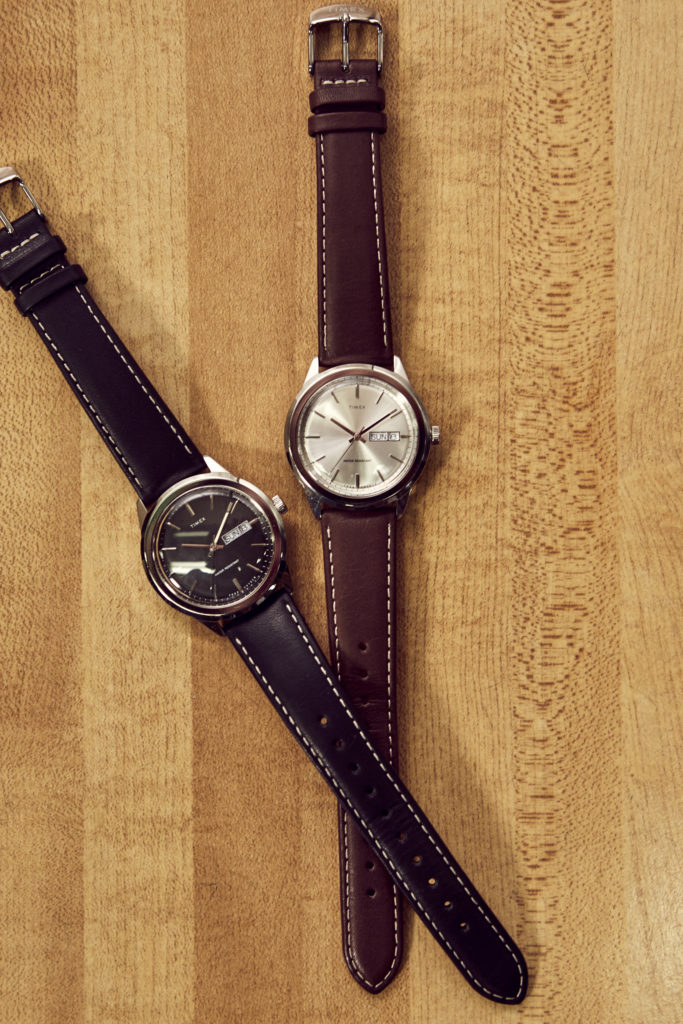 Two silver Waterbury watches with black and brown straps