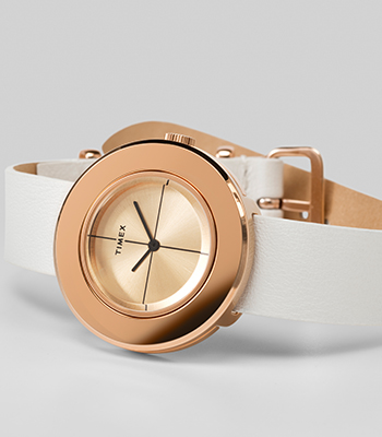 Timex Rose Gold watch with white leather laying sideways in front of white background