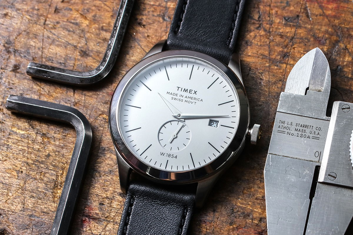 Up close view of Black Strap/White Dial American Documents watch with watchmaking tools around it.
